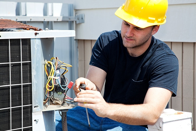 Man repairing HVAC. At Your Service Heating and Air