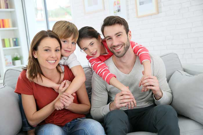 Family on Couch At Your Service Heating and Air Conditining